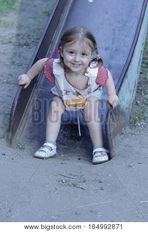 Children slide down near the house or in the park. Happy little girl 2-3 years slid from slide