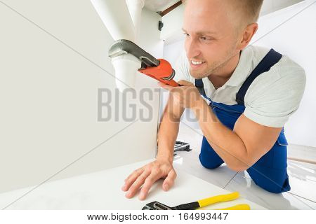 Happy Young Male Plumber Fixing Sink Pipe With Adjustable Wrench