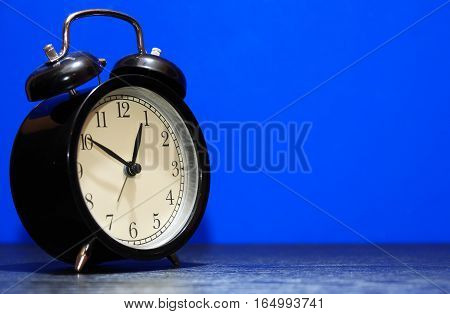 Vintage black alarm clock on blue background with free space for text