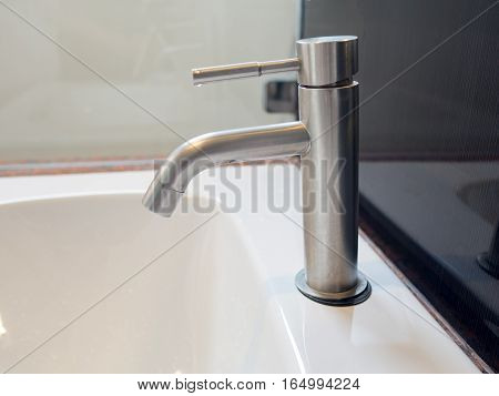 Modern classic metal faucet in toilet at home.