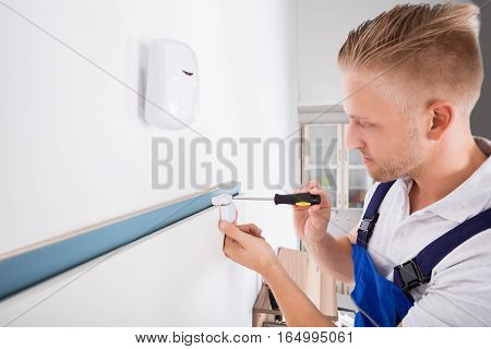 Close-up Of Technician Installing Security System Door Sensor Using Screwdriver