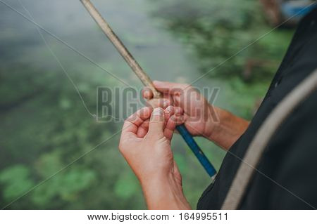 Fishing rod with a hook in the hands of the fisherman