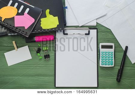 Workplace with folder with a blank sheet of paper notepads business card and other office supply on a desk with copy space top view. Blank template for design mock-up. Office desk flat lay.