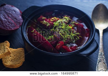 Vegetable soup - red borsch in the pot on a black slate board. Healthy beetroot soup vegetarian food. Delicious beet soup with croutons.