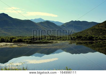 Picture  Skadar lake with mountains with azure sky.