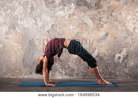 Young man doing yoga or pilates exercise in urban background. Advanced Bridge pose chakrasana.