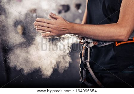Climber woman coating her hands in powder chalk magnesium and preparing to climb indoor close-up
