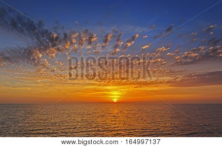 Beautiful sunset at Ijsselmeer sea with clouds illuminated by sun, The Netherlands