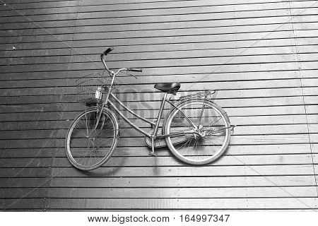 Black and white picture of bicycle laying on the wooden floor