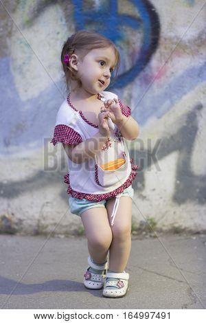 Shy kid girl with pigtails on a background of a concrete wall with paint pattern