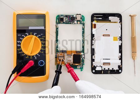 High Angle View Of Person Checking Damaged Mobile Phone With Digital Multimeter