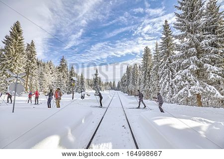 Jakuszyce Poland - January 07 2017: Cross-country skiers passing railroad track in forest.