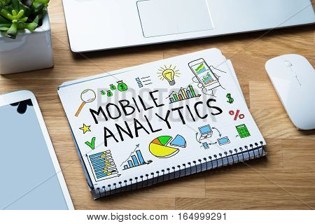High Angle View Of Mobile Analytic Concept On Binder At Wooden Desk In Office