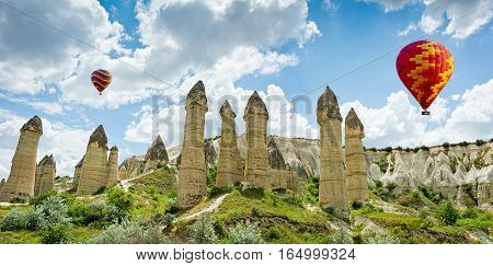 Hot air balloons flying over Love valley at Cappadocia Anatolia Turkey. Volcanic mountains in Goreme national park.