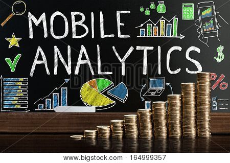 Stack Of Coins In Front Of Blackboard Showing Mobile Analytic Concept