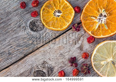 Dried orange and lemon fruits on the wooden background.