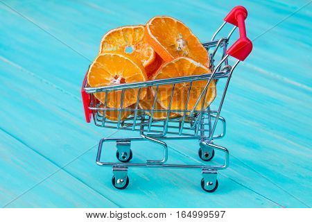 Dry orange with shopping cart on blue wooden kitchen table background