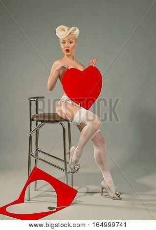 Young girl holding red heart in her arms. Emulation of Pin-Up style photography