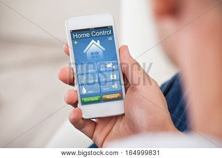 Close-up Of Person Hand Using Home Control System On Mobilephone