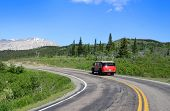 Red tour bus on road in scenic Glacier national park poster