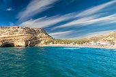 Tourists relax and bath in crystal clear water of Matala in south of Creta. There are many caves near the beach. poster