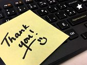 Thank you note on office computer keyboard handwritten with smile to thank employee, co-worker or colleague and express appreciation with hashtag key #thankyou an s words appreciation poster