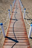 Wooden walkway over the sand dunes to the beach. Beach pathway in Lido di Ostia ( Lido di Roma) private beach Salvataggio Italy. poster