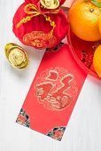 Chinese New yearred envelope packet (ang pow) and red felt fabric bag with gold ingots and oranges and flower on white wood table topChinese Language mean Happiness poster