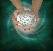 Lucky Lottery Numbers 1 to 59 - female hands cupped around a large crystal ball with random lottery numbers emerging  on a  green black spiraling energy field background with copy space below poster