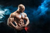 Strong bald bodybuilder with six pack. Bodybuilder man with perfect abs, shoulders, biceps, triceps and chest, personal fitness trainer flexing his muscles in blue, red smoke poster