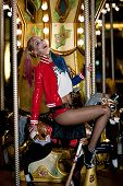 Smiling cosplayer girl in costume Harley on background lights of carousel ride. Cosplay poster