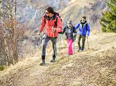 Tour scout guide bringing young couple for trekking excursion - People hiking high mountain in france - Survivaltravel and adventure concept - Focus on left man face - Warm vivid filter poster