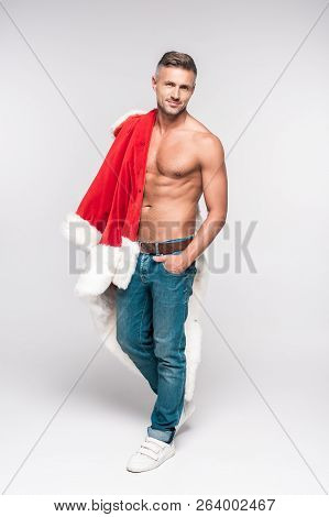 Full Length View Of Handsome Shirtless Man With Santa Costume On Shoulder Standing With Hand In Pock