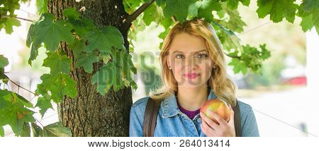 Girl student with backpack hold apple while stand near tree. Students life concept. Take minute to relax. Break for snack. Student eat apple fruit nature background defocused. Healthy snack poster