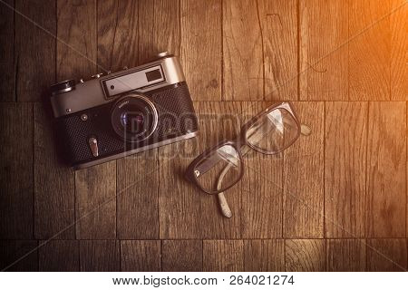 Vintage Camera With Glasses On A Wooden Background. Close-up