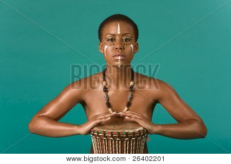 Portrait of African American woman wearing original tribal themed face-paint and necklace playing Conga drum