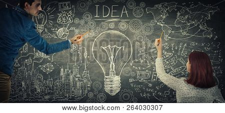 Man And Woman Sharing Thoughts Together Drawing A Big Light Bulb Sketch On Blackboard. People Ideas