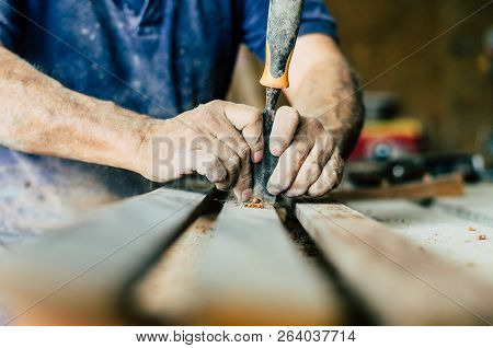 Professional Carpenter At Work, He Is Carving Wood Using A Woodworking Tool, Hands Close Up, Carpent