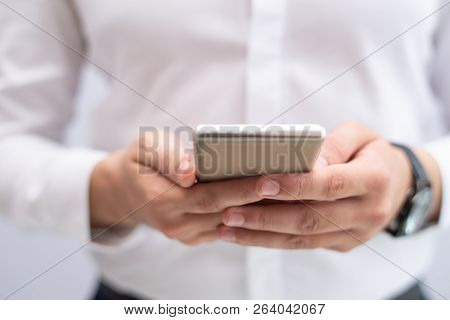 Close-up Of Young Businessman Networking On Mobile Phone. Caucasian Man Reading Message Or Browsing
