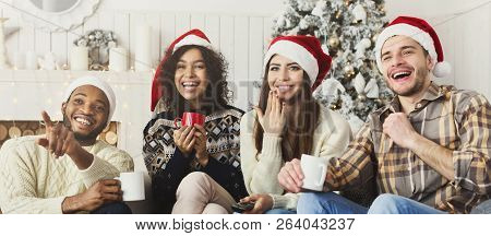 Christmas Comedy Show. Happy Laughing Friends In Santa Hats Watching Tv Together At Home, Copy Space