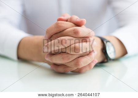 Close-up Of Man Sitting At Table And Clasping Hands. Confident Unrecognizable Businessman Clenching