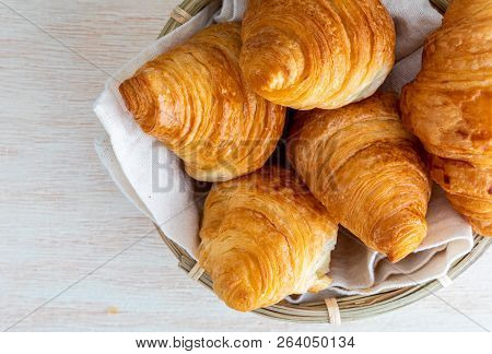 Butter Croissants In Small Wicker Basket. Aerial (top) View On Clear Wood Background.