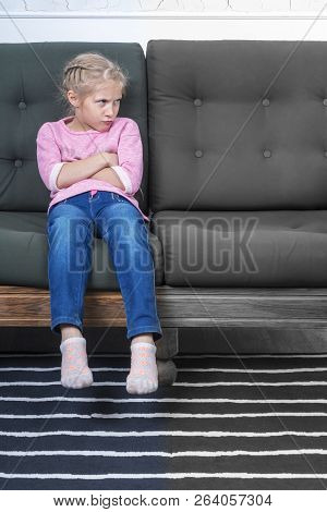 Young Offended Girl With Pouting Lips Sitting On The Couch And Looking Sideways