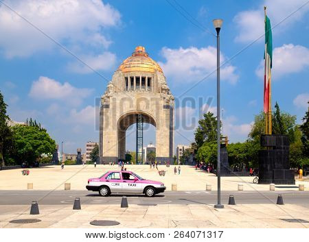 MEXICO CITY,MEXICO - JULY 12,2018 : White and pink taxi in front of the Monument to the Revolution in Mexico City