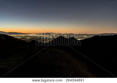 Los Angeles California predawn view of hilltop ridgeline above the San Fernando Valley.  Burbank, North Hollywood and the San Gabriel Mountains are in background.