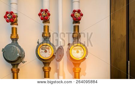 Single Water Meter And Valves On White Concrete Wall Of House. Water Consumption And Bill Concept. W