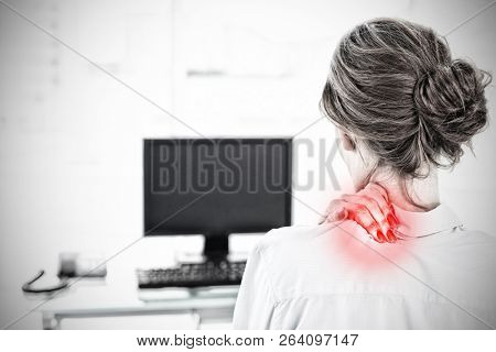 Rear view of a businesswoman with neck pain in office against highlighted pain