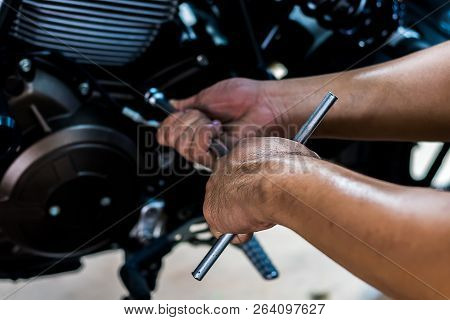 Image Is Close Up. People Holding Hand Are Repairing A Motorcycle Use A Wrench And A Screwdriver To