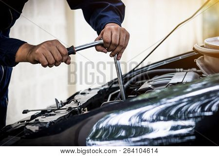 A Man Mechanic Are Repair A Car Use A Wrench And A Screwdriver To Work.