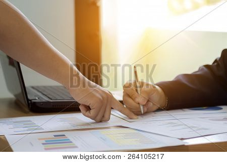 Business Man Working At Office Desk With Laptop, Employees Are Pointing Fingers A Paper Chart Plan M